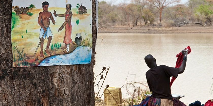 <p>A woman does her washing near a dam in the country now known as South Sudan. Nearby, a sign cautions against entering The water while infected with Guinea worm disease. (Photo: The Carter Center/L. Gubb)</p>